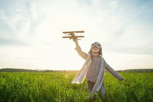 Little boy with wooden airplane in the field - ADHD